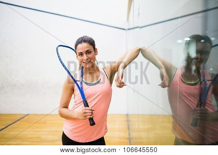 Smiling woman holding a squash racket in the squash court