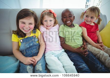 Happy kids laughing while sitting down on the couch