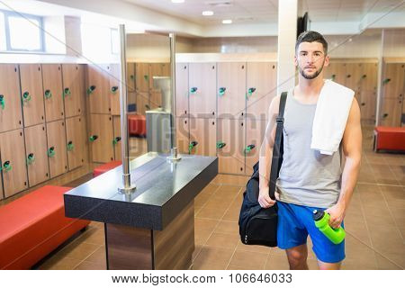 Smiling man about to go to the gym in the gym locker room