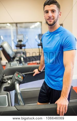 Smiling man standing on a treadmill at the gym