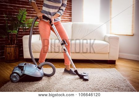 Woman hoovering the rug at home in the living room