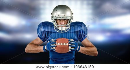 Portrait of confident sports player holding ball against sports pitch
