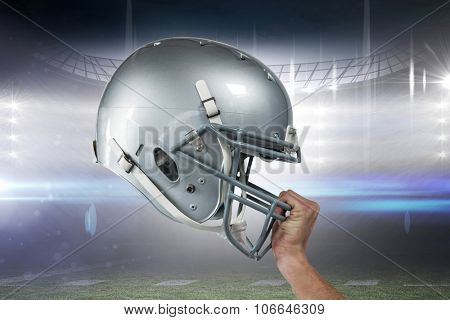 Close-up of American football player handing his sliver helmet against american football arena