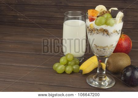 fresh milk in the glass and muesli breakfast on a wooden table.