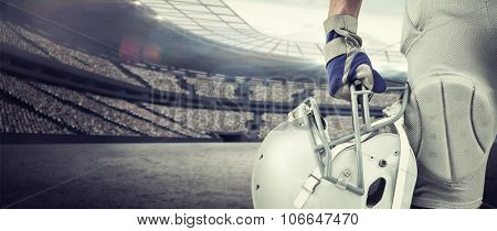 Close-up of American football player holding helmet against rugby stadium