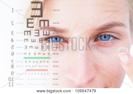 Pretty blonde applying contact lens against eye test