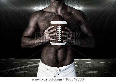 Midsection of shirtless rugby player holding ball against spotlight