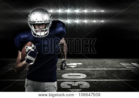 Confident American football player running with ball against spotlights