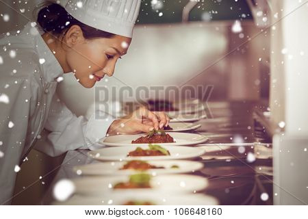 Snow against concentrated female chef garnishing food in kitchen
