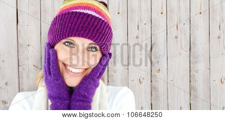 Radiant young woman with cap and gloves in the winter against wooden background