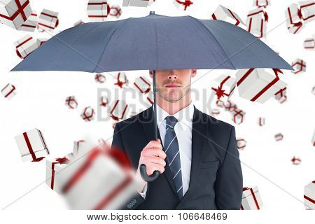 Unsmiling businessman sheltering under umbrella against white and red gift box
