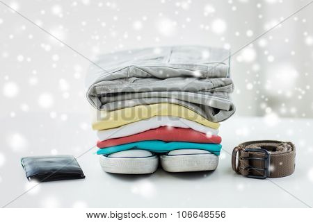 clothes and personal staff concept - close up of folded shirts, pants, belt, wallet and shoes on table at home over snow effect