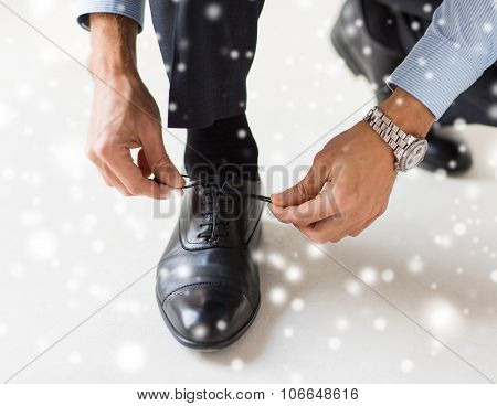 people, business, fashion and footwear concept - close up of man leg and hands tying shoe laces over snow effect over snow effect