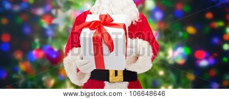 christmas, holidays and people concept - close up of santa claus with gift box over lights background