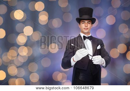 performance, circus, people and show concept - magician in top hat with magic wand over nigh lights background