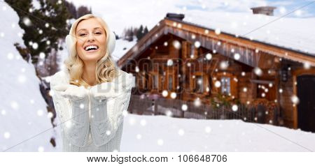winter, advertisement, vacation, christmas and people concept - smiling young woman in earmuffs and sweater holding something on her empty palms over wooden country house and snowflakes background