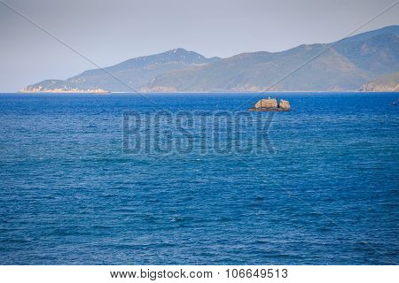 Fishing Boat Amidst Azure Sea Against Hilly Tropical Island