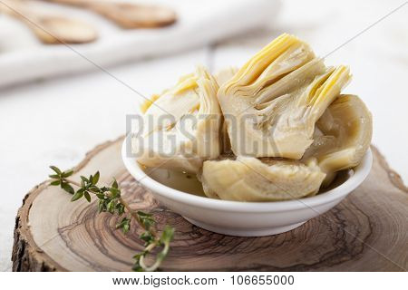 Artichoke hearts marinated in olive oil a small white bowl
