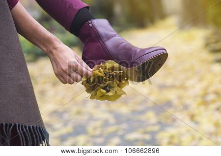 Closeup Of Woman's Shoe With Leaves Stuck On Her Heal