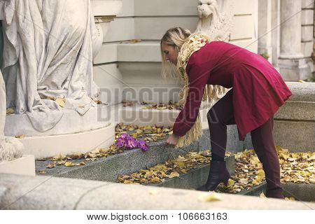 Woman Putting A Flower On Tombstone