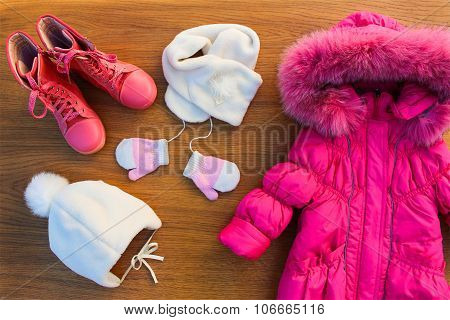 Children's winter clothes: warm pink jacket, hat, scarf, mittens, boots