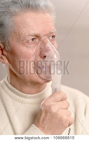 Elder man making inhalation