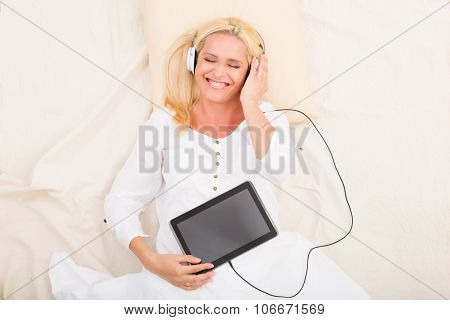Woman With Headphones And Tablet In Bed.....