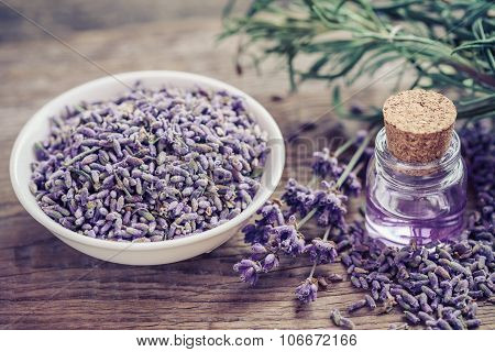 Bottle Of Essential Oil And Lavender Flowers In Bowl And On Table.