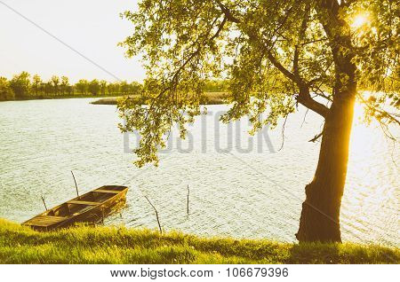 summer landscape - wooden boat, backwater, tree and sunset.
