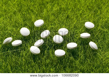 White antibiotic pills scattered on the grass