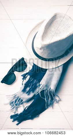 hat and blue with sunglasses scarf on white table vintage style