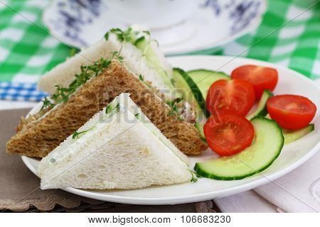 White and brown cream cheese and cucumber sandwiches with green salad