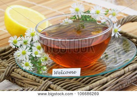 Welcome card with cup of chamomile tea with fresh chamomile flowers and lemon