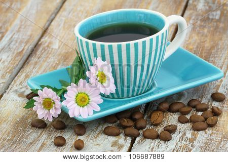 Cup of coffee and pink daisy flowers on rustic wooden surface