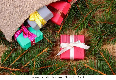 Wrapped Gifts In Jute Bag For Christmas Or Other Celebration And Spruce Branches