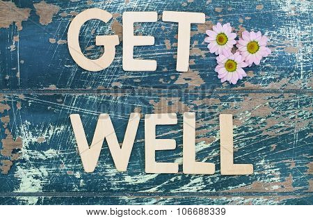 Get well written on rustic wooden surface and pink daisies