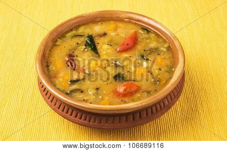 south indian vegetable sambar, in earthen bowl on yellow background