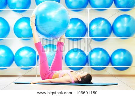 woman lying on the fitness mat lifting exercise ball using her legs as part of workout routine