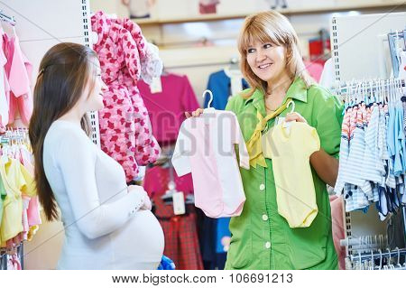 Pregnancy shopping. Female saleswoman selling newborn clothes to young pregnant woman at baby shop store