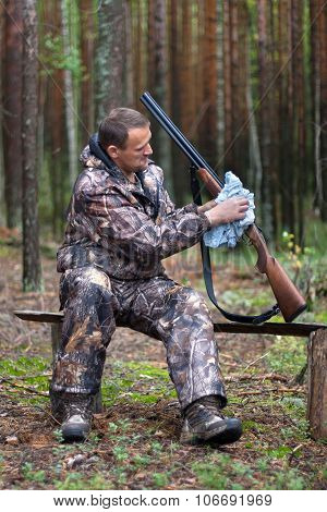 Hunter Cleaning Shotgun In The Forest Camp