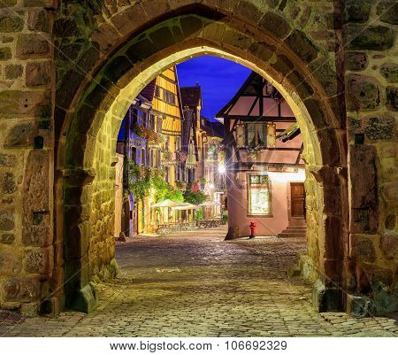 View Of Riquewihr, Alsace, France, Through City Wall Gate At Night