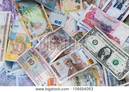 Many banknotes of different countries scattered on the table