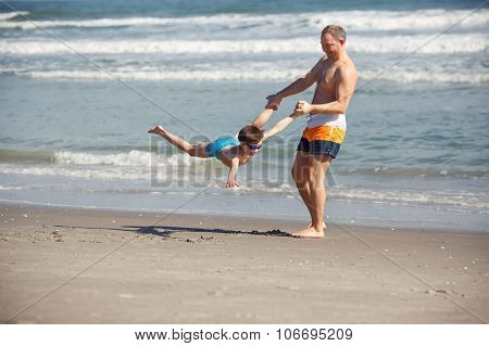 Father and son having fun on a tropical beach