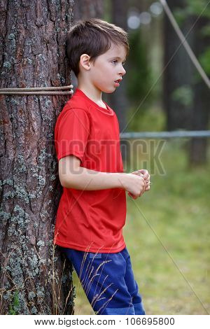 Sad little boy standing under the tree
