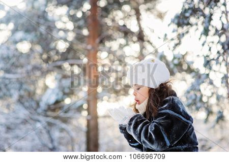 child playing with snow on cozy winter forest walk