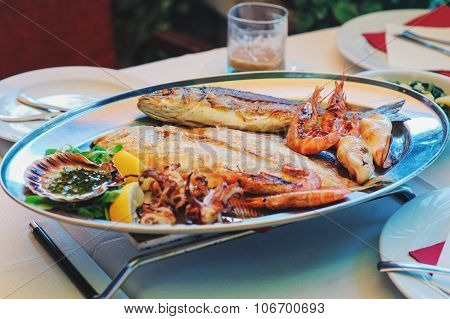 traditional slovenian and croatian cuisine - mixed grilled fish and seafood with garlic oil