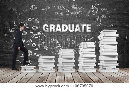 A Man Is Going Up Using A Stairs Which Are Made Of White Books. The Word Graduate Is On The Black Ch