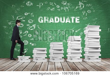 A Man Is Going Up Using A Stairs Which Are Made Of White Books. The Word Graduate Is On The Green Ch