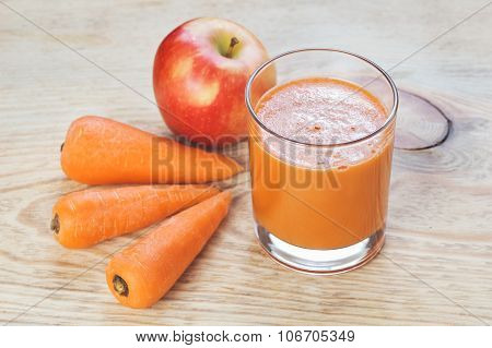 Glass of homemade juice, apple and carrot on wooden board