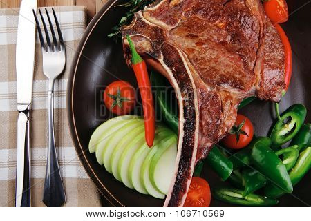 meat food : grilled beef spare rib on dark dish with thyme pepper and tomato on wooden table